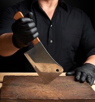 Lo chef in camicia nera e guanti in lattice nero tiene in mano un grosso coltello da cucina
