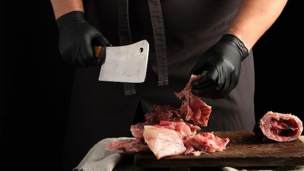 Lo chef in guanti di lattice nero tiene un grosso coltello e taglia a pezzi la carne di coniglio cruda su un tagliere di legno marrone