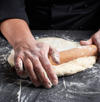 Lo chef in una tunica nera tira un impasto per una pizza rotonda