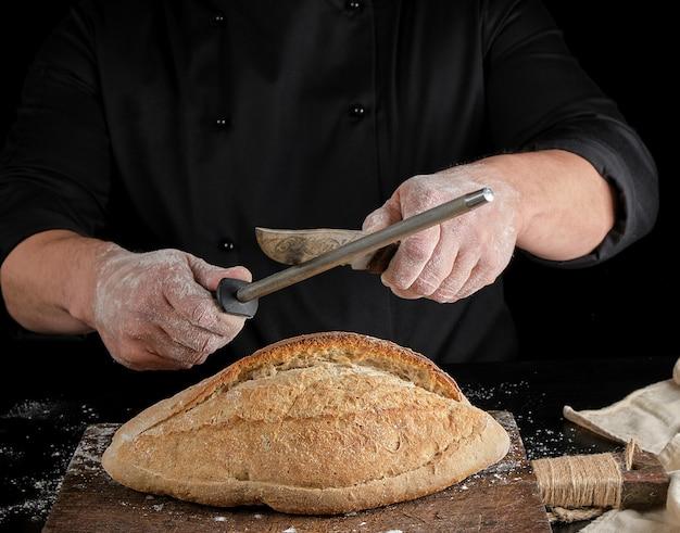 Lo chef in uniforme nera affila un coltello da cucina