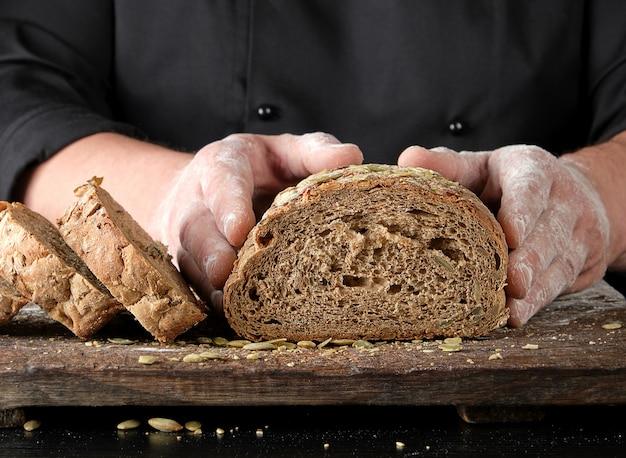 Lo chef in uniforme nera continua a tagliare un pezzo di pane cotto con farina di segale