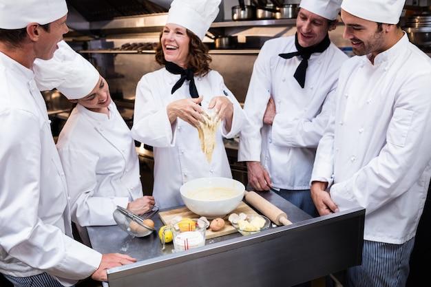 Lo chef insegna alla sua squadra a preparare un impasto