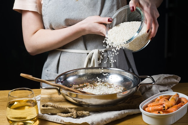Lo chef mette il riso nella padella per il risotto italiano. gamberi, vino bianco, riso, cipolle, timo, aglio.