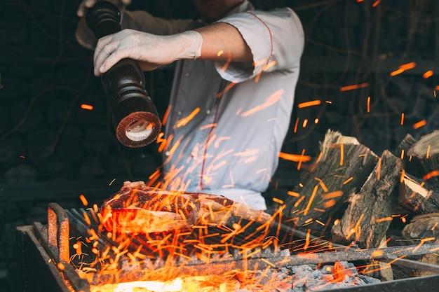 Lo chef pepa la bistecca sul fuoco.