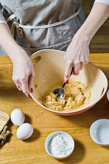 Lo chef prepara biscotti di farina d'avena, mescola zucchero di canna e burro. ingredienti fiocchi d'avena, burro, zucchero, uova, cioccolato.