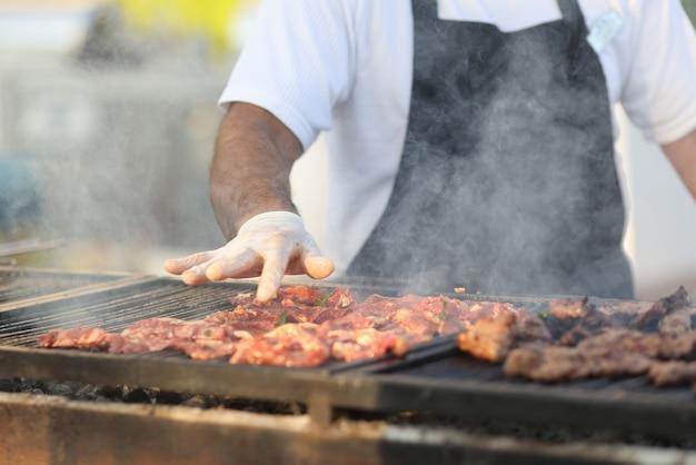 Lo chef prepara carne alla griglia