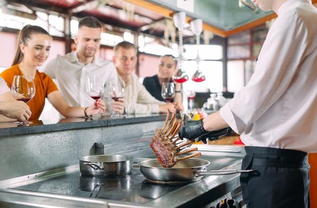 Lo chef prepara cibo davanti ai visitatori del ristorante