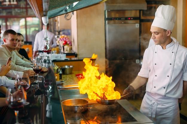 Lo chef prepara cibo davanti ai visitatori nel ristorante