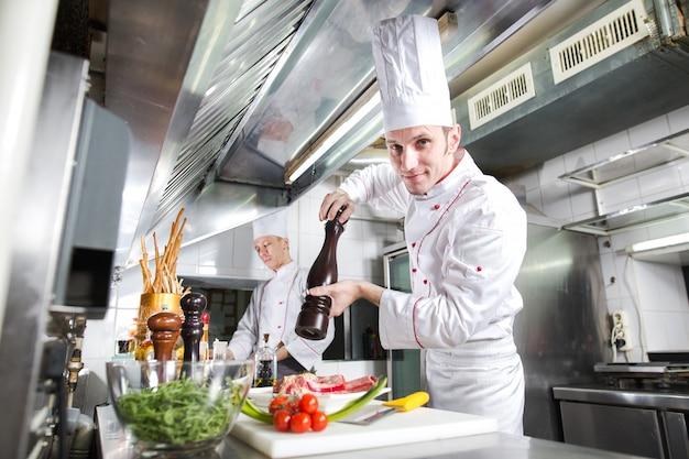 Lo chef prepara un piatto nella cucina di restoran.