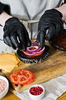 Lo chef raccoglie gli ingredienti di un cheeseburger. il concetto di cucinare un hamburger nero. ricetta hamburger fatta in casa.