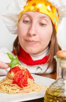 Lo chef sorridente guarnisce un piatto di pasta italiana