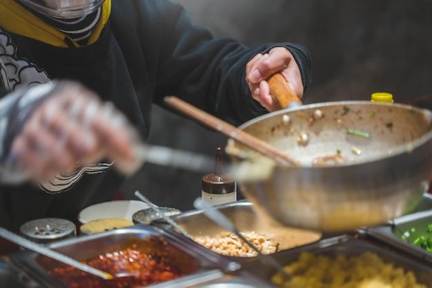 Lo chef sta cucinando cibo cinese