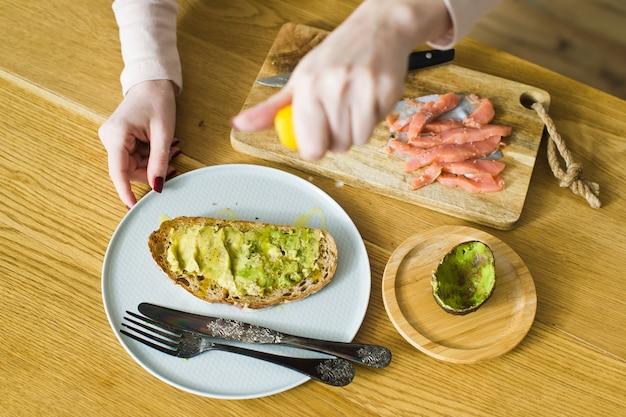 Lo chef stringe un toast al limone con avocado su pane tostato di pane nero.