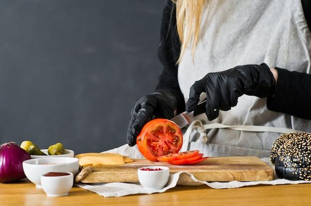 Lo chef taglia i pomodori rossi. il concetto di cucinare un hamburger nero.