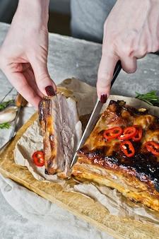 Lo chef taglia la griglia delle costolette di maiale.