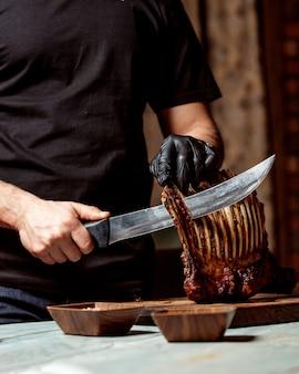 Lo chef taglia le costolette di agnello fritto