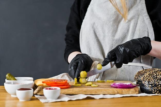 Lo chef taglia sottaceti. il concetto di cucinare un hamburger nero. ricetta hamburger fatta in casa.