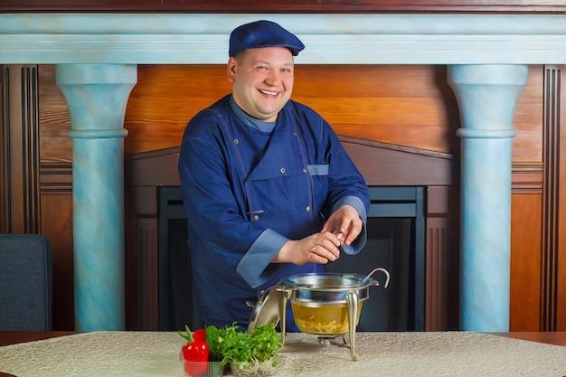 Lo chef versa le spezie nella pentola con la zuppa. spezie di versamento alla zuppa. ritratto.