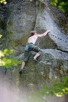 Lo scalatore muscolare scala sulla parete della scogliera con la corda
