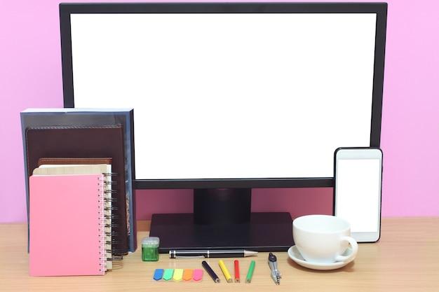 Lo schermo bianco del computer portatile e i libri sono posizionati sulla scrivania.