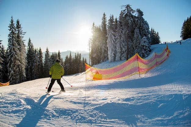Lo sciatore che guida sulla neve fresca scende la stazione sciistica in montagna al giorno soleggiato