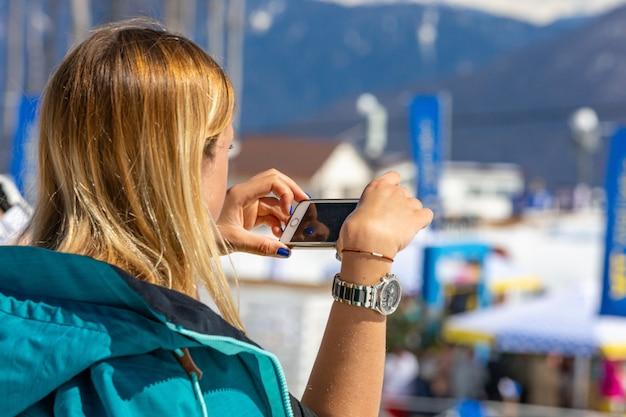 Lo sciatore fa una foto del paesaggio montano