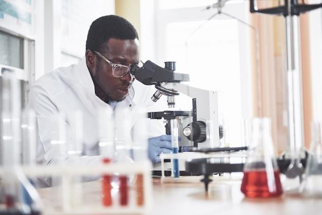 Lo scienziato lavora con un microscopio in un laboratorio conducendo esperimenti e formule.