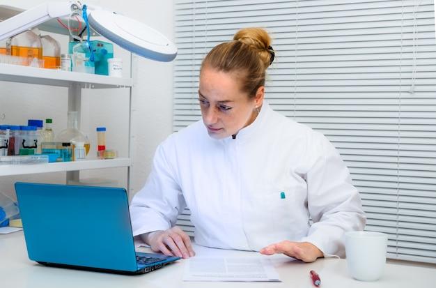 Lo scienziato legge documenti sul computer in laboratorio