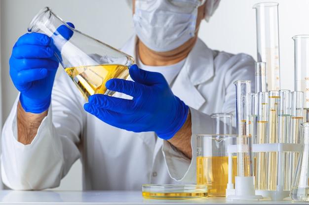 Lo scienziato passa la tenuta del liquido in una vetreria in laboratorio per analisi