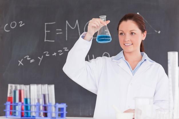 Lo scienziato sveglio che esamina un contenitore ha riempito di liquido blu