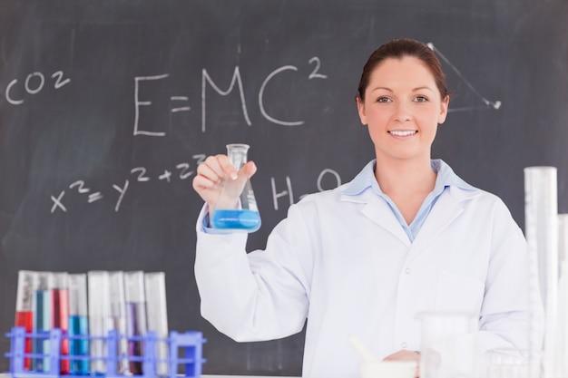 Lo scienziato sveglio che tiene un contenitore ha riempito di liquido blu