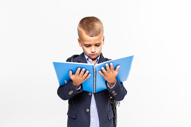 Lo scolaro con il libro in mano su un muro bianco