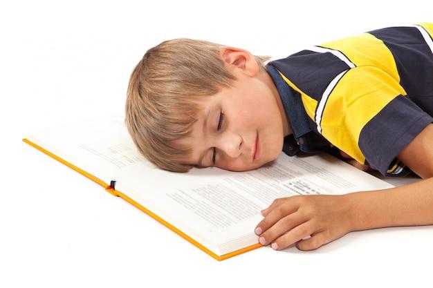 Lo scolaro sta dormendo su una priorità bassa bianca