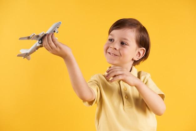 Lo scolaro sta giocando con l'aeroplano di modello.