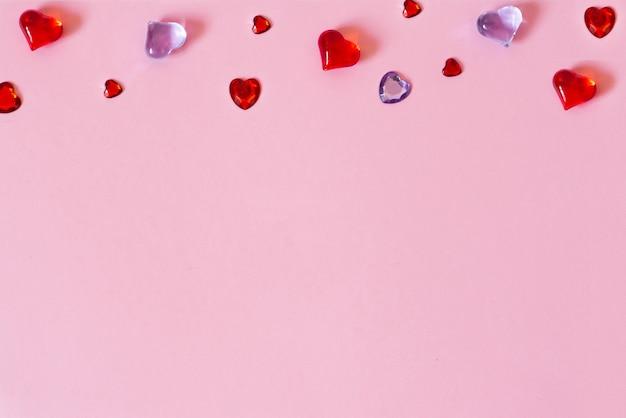 Lo sfondo di san valentino. bordo di bellissimi cuori diversi su uno sfondo rosa