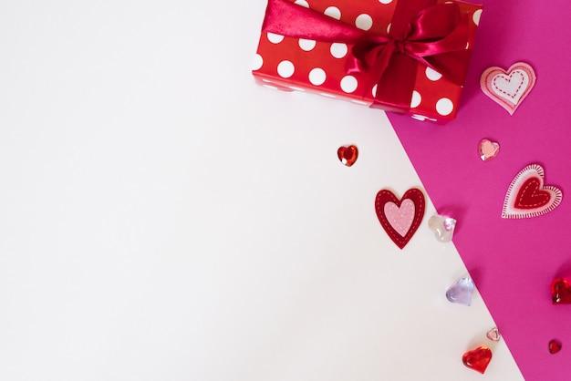 Lo sfondo di san valentino. scatola regalo rossa con nastro di raso rosso e tanti cuori diversi