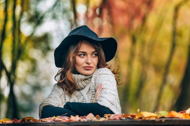 Lo sguardo di una bella signora con un cappello nero è diretto di lato.