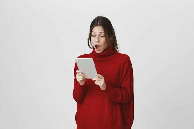 Lo sguardo stupito della ragazza all'esposizione digitale della compressa ha colpito