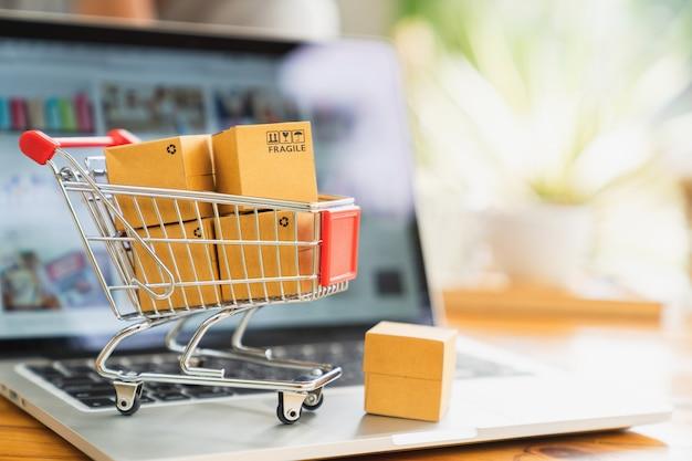 Lo shopping online e il concetto di consegna, scatole del pacchetto di prodotti nel carrello e laptop