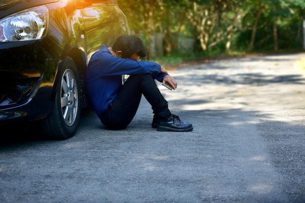 Lo smart phone della tenuta dell'uomo deludente e sedentesi all'auto ha parcheggiato sulla strada