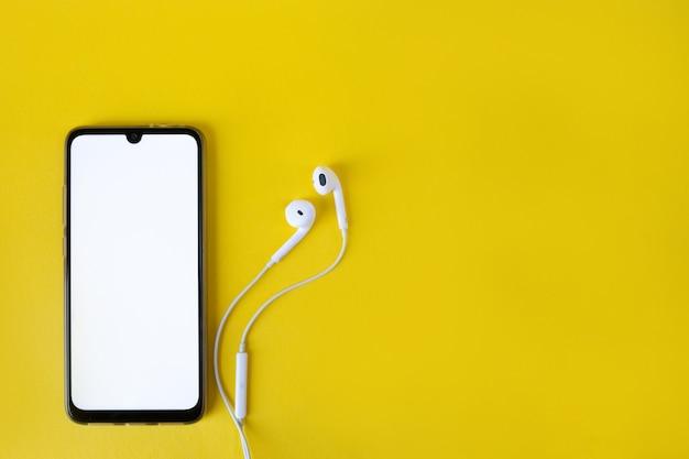 Lo smartphone con lo schermo bianco in bianco si collega alle cuffie sulla vista superiore gialla. auricolare collegato al cellulare.