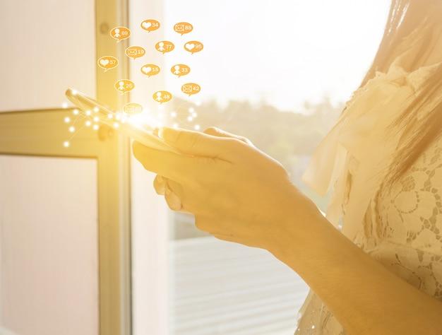 Lo smartphone della tenuta della donna e ha un messaggio per entrare nei social media dello smartphone