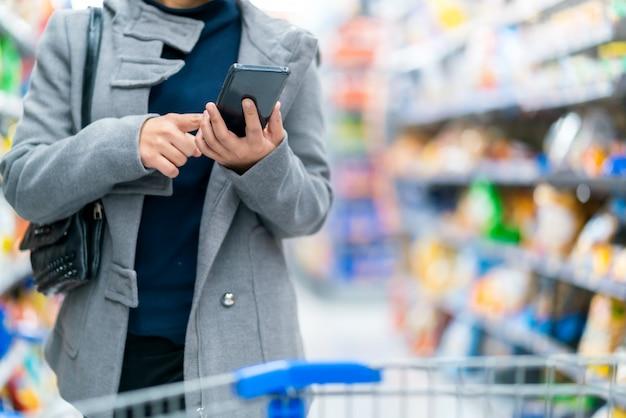 Lo smartphone femminile asiatico della tenuta della mano del primo piano che controlla il prezzo confronta in supermercato con il kart di acquisto del carrello