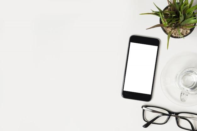 Lo smartphone nero con lo schermo bianco in bianco del mockup è sopra il tavolo bianco dell'ufficio.