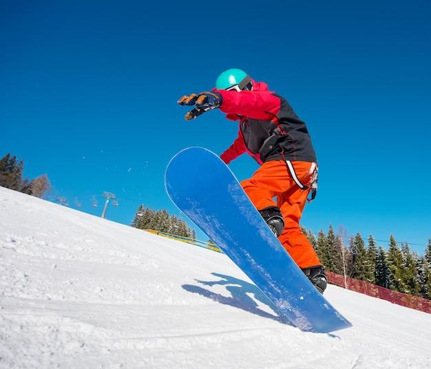 Lo snowboarder che salta nell'aria mentre guida sul pendio alla stazione sciistica dell'inverno nelle montagne