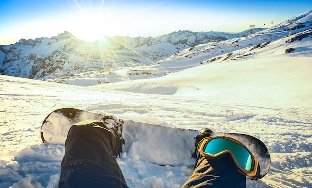 Lo snowboarder che si siede sopra si rilassa il momento al tramonto sulla montagna nevosa