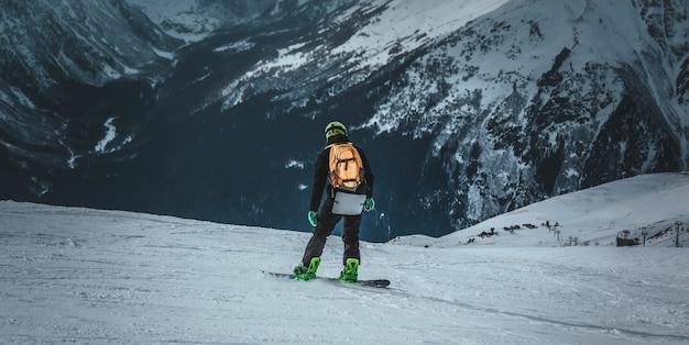 Lo snowboarder dell'uomo guida sul pendio. stazione sciistica. spazio per il testo