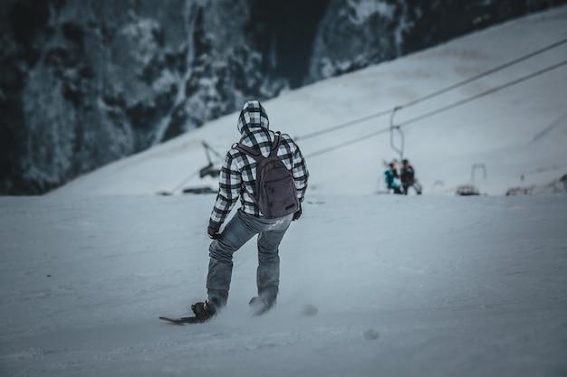 Lo snowboarder dell'uomo guida sul pendio. stazione sciistica.