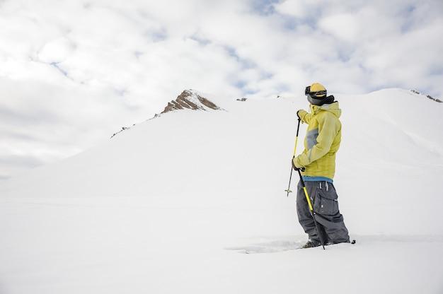 Lo snowboarder di freeride si è vestito in abiti sportivi gialli che esaminano la montagna