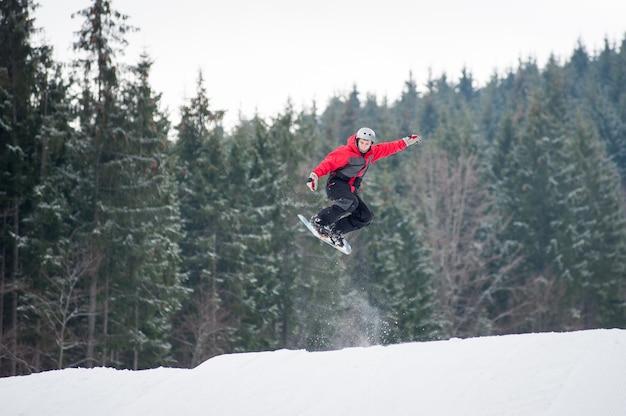 Lo snowboarder maschio che salta sopra il pendio in giornata invernale